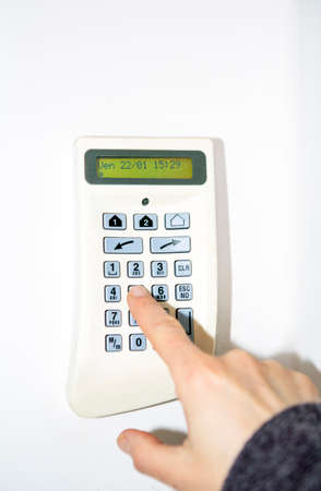 Alarm system, woman's hand entering the code in security panel to unlock the alarm