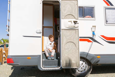 little curly-haired boy smiling sitting in the door of motor home, tenderly holding his pet.