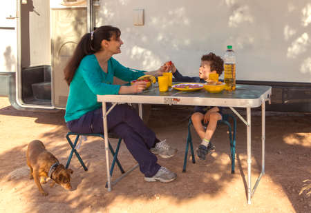 boy with his mother and puppy having a picnic on a table in front of the motor-home