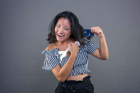 Happy and smiling young chinese woman showing credit card