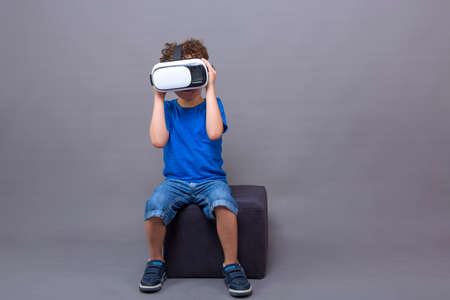 curly-haired Caucasian boy sitting and playing with virtual reality goggles