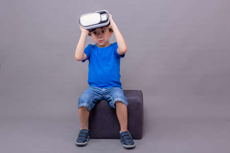 Child holding up virtual reality goggles with an astonished expression