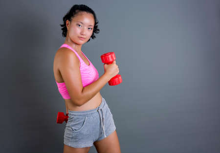 young chinese girl exercising with dumbbells looking straight ahead Banque d'images