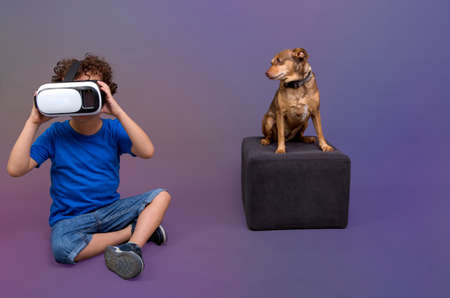 little boy playing with virtual reality glasses next to his little dog who looks at him in amazement