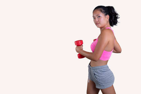 pretty chinese exercising with dumbbells facing forward on white background