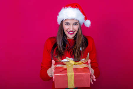 beautiful young woman in red sweater and Santa Claus hat offering a gift with a big smile