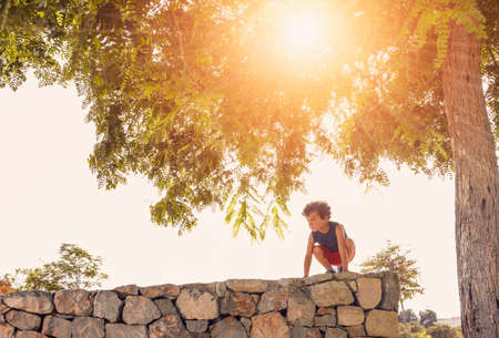 a little boy enjoys climbing a stone wall, under a tree through which the sun's rays enter at sunset. Banque d'images