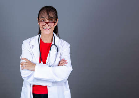 40-45 year old female doctor with glasses, arms crossed looking straight ahead and smiling