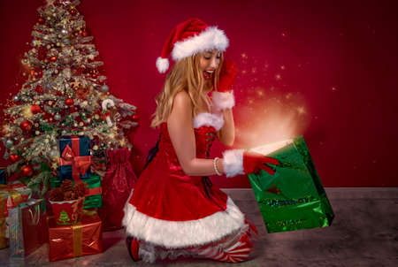 cute girl dressed as Santa Claus, looking in a gift bag with a glow and stars, behind the Christmas tree and gifts.