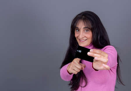 Caucasian brunette woman with long hair, smiling, showing credit card