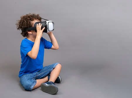 child sitting and playing with virtual reality goggles