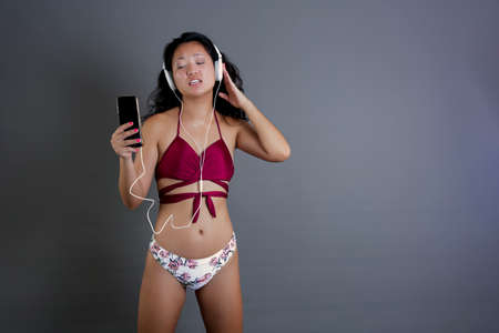 cute and funny chinese in bikini listening to music from smart-phone and headphones Banque d'images