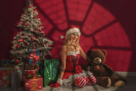 blonde woman in Santa Claus costume with gifts and Christmas tree illuminated by light coming from a skylight, and accompanied by a large teddy bear.