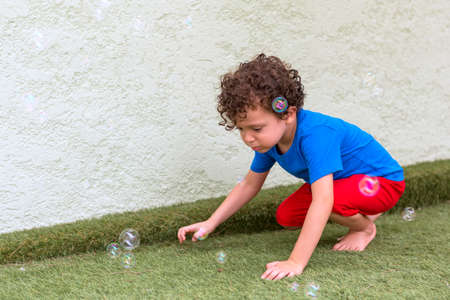 beautiful 4-5 year old caucasian boy with curly hair in his backyard playing with soap bubbles Banque d'images
