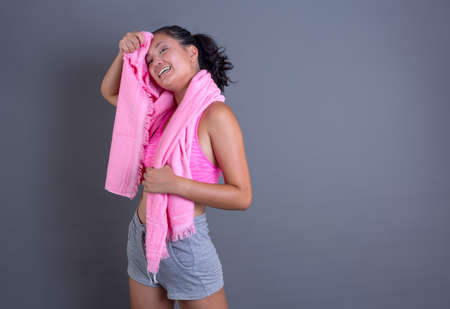 pretty brunette chinese girl in sportswear and wiping sweat with towel on gray background.