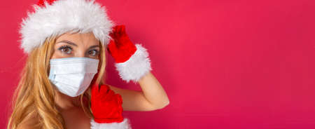 beautiful young Caucasian blonde with Santa Claus hat and gloves, close-up with mask. and copy-space. Banque d'images