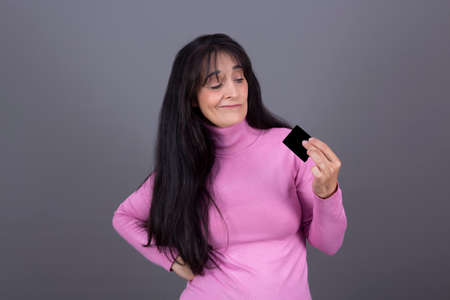 pretty caucasian woman with long black hair in her 40s looking at card in her hand with disapproving face Banque d'images