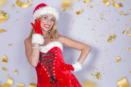 young girl dressed as Santa Claus, smiling on a white background and falling golden streamers around her