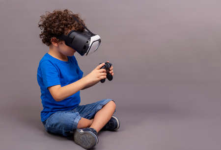 4-5 year old Caucasian boy sitting on the floor with virtual reality goggles and game controllers in his hands