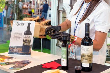 Alicante, spain. 09-26-2021 woman serving wine (Altos de Orihuela) for tasting at the gastronomic fair in Alicante. Éditoriale