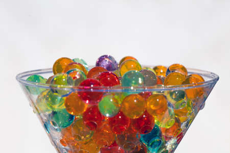 on white background and sunlight, glass cup full of semitransparent multi-colored beads, selective focus and artistic blur.