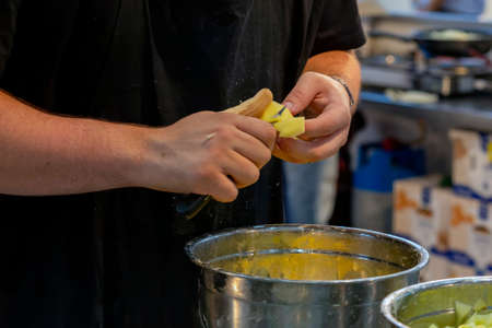 cook cutting potatoes into small pieces to make the typical Spanish meal, tortilla de patatas. (potato omelet) Banque d'images