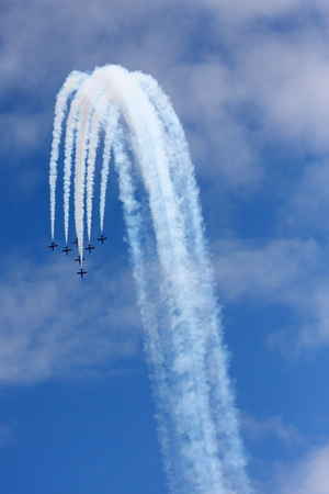 pirouette: planes group in acrobatic flight with smoke trace over blue sky Editorial