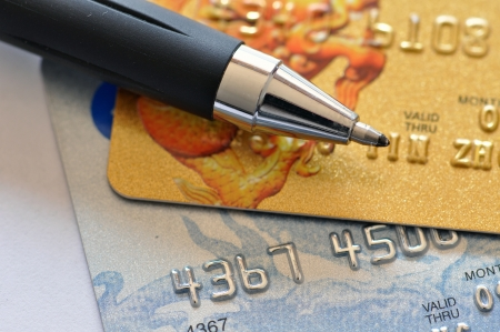plastic money: Credit card and pen