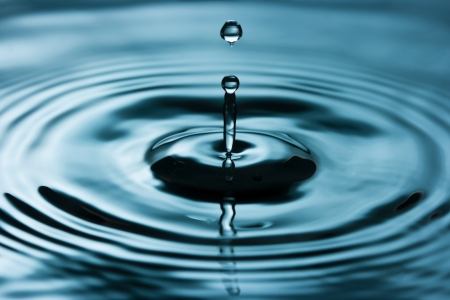 A drop of water above water surface - water splash two drops clash.