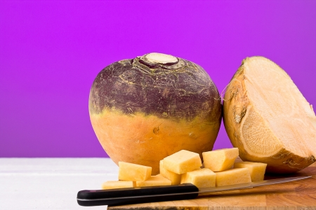 swede: Large Swede chopped into square chunks on a chopping board with purple background and copy space.