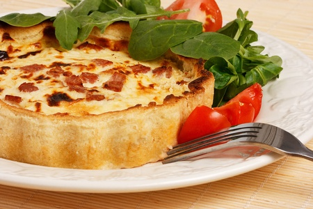savoury: Close- up  of  Quiche Lorene with Lettuce and tomatoes salad on a plate.