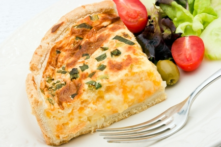 A delicious quiche with cheese and leeks on a white plate and a salad of  mixed lettuce, tomatoes, olives and cucumber.    photo