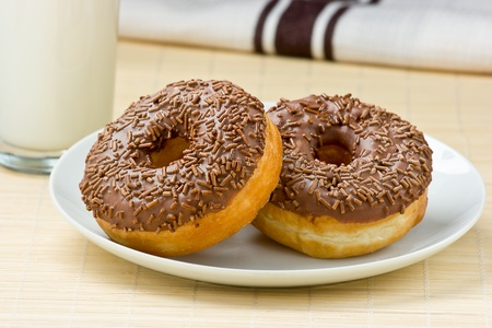 doughnut: Close Up Of Two Chocolate Doughnuts On A Plate With &  A Glass Of Milk.