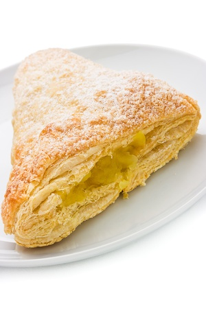turnover:  Apple turnover with a tasty sweet apple filling oozing out of  flaky puff pastry and icing sugar sprinkled on top. Shallow dof   Stock Photo
