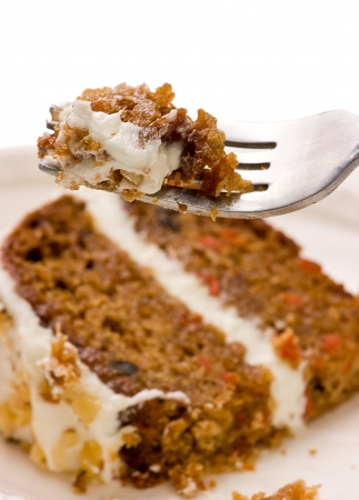 cake with icing: Close up of  creamy sweet walnut carrot cake on a fork with white background.