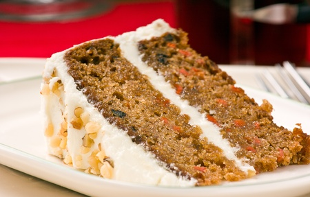 Sweet slice of walnut carrot cake on white plate. Shallow depth of field.  photo