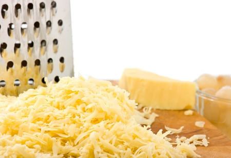 shredded cheese: Grated mild cheddar cheese on wooden board with grater and pickled onions focus on forground. White background for copy space. Stock Photo