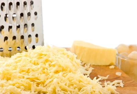 queso rallado: Queso rallado Cheddar suave sobre tabla de madera con un rallador y el enfoque cebolla en escabeche en el primer plano. El fondo blanco por espacio de copia.