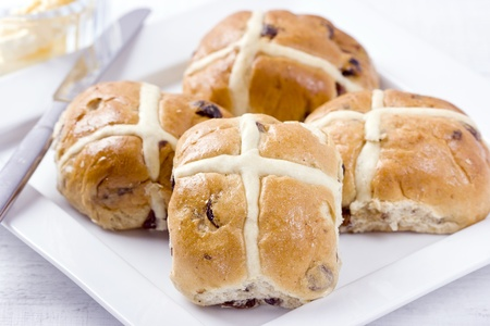 buns: Hot Cross Buns  Traditional Easter spiced, sticky glazed fruit buns with crosses on white dish with butter dish and knife