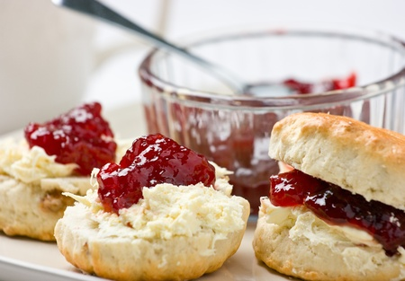 scones: Home-baked scones tea with strawberry jam and clotted cream. Shallow depth of field. Stock Photo