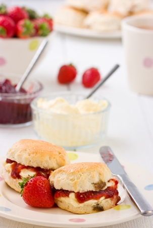 scones: Summer time on a plate with scones, strawberry jam, clotted cream strawberries, and tea on a white rustic table.