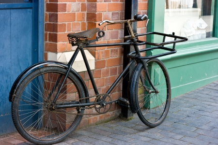 Old Victorian Bicycle Standing Outside A Victorian Shop Window. photo