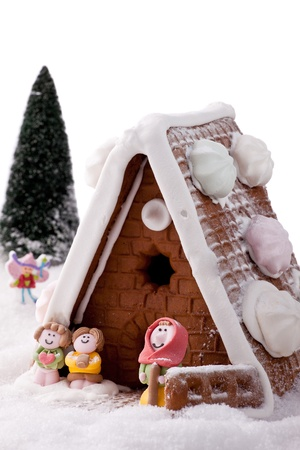 Gingerbread house on fake snow with model characters on white background.    photo