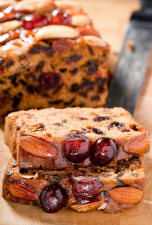 traditon: Christmas fruitcake slices garnished with cherries almonds and brazil nuts on chopping board.
