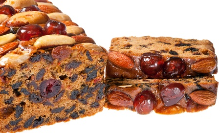 fruitcake: Christmas fruitcake slices with cherries almonds and brazil nuts. on white background.