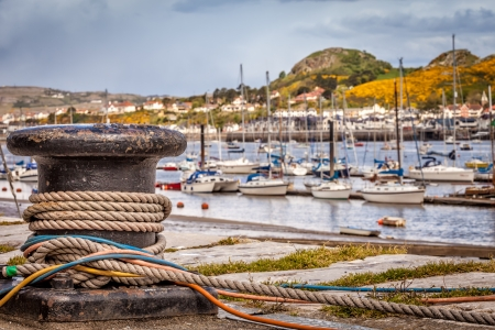 mooring: Close up view of harbour bollard with mooring ropes and colorful cables wrapped around it  A Senic view with sailing boats and  the Welsh hills in the distance