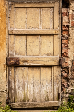 Old wooden exterior door with worn cracked yellow paint and rusty lock photo