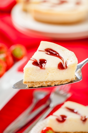 vertical composition: Strawberry Cheesecake slice sitting on cake knife with strawberries and red background  Vertical composition  Stock Photo