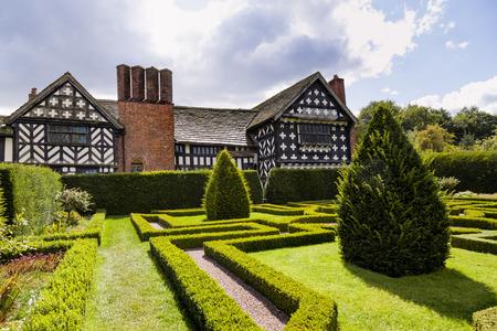 tudor: Tudor Knot Garden with yew trees next to a 16th century Tudor house Editorial