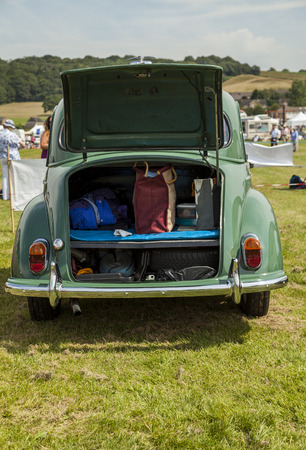 morris: Morris Minor Classic car parked in a field with rear boot lid (trunk lid)  open displaying its contents inside shopping bag, cookies in a box, and more.